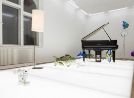 """Philippe Pareno, """"Quasi Objects: My Room is a Fish Bowl, AC/DC Snakes, Happy Ending, Il Tempo del Postino, Opalescent acrylic glass podium, Disklavier Piano"""", various helium inflatable float balloons in the shape of fish, electrical plugs and adapters, lamp with Arne Jacobsen lampshade, electrical system, electrical wire and plug, magnifying glass, opalescent acrylic glass podium, LED lights, 6 plugs, 194,5 x 600 x 300 cm, 2014 (image courtesy the artist and Esther Schipper, Berlinl Photo © Andrea Rossetti)菲利普·帕雷诺,""""Quasi Objects: My Room is a Fish Bowl, AC/DC Snakes, Happy Ending, Il Tempo del Postino, Opalescent acrylic glass podium, Disklavier Piano"""", (准物体:我的房间是鱼缸,AC/DC蛇,美满结局,邮递员节奏,乳白色丙烯酸玻璃台,Disklavier钢琴),各种鱼形充氦漂浮气球,电插头和适配器,阿内·雅克布森灯形的灯,电子系统,电线和插头,放大镜,乳白色丙烯酸玻璃台,LED灯,6个插头,194.5 x 600 x 300 cm, 2014(图片惠与:the artist and Esther Schipper, Berlin; Photo © Andrea Rossetti)"""