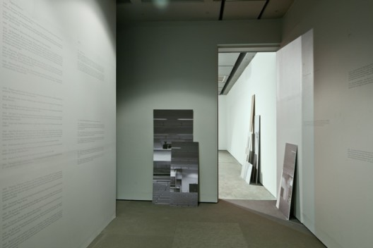 "Hito Steyerl, installation view. ""Adorno's Grey (2012)"", Single Channel HD video projection, 00:14:20, Four angled screens, wall plot, photographs. Copyright Hito Steyerl, courtesy Wilfried Lentz Rotterdam."