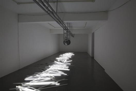 """张培力,《碰撞的和声》, 声音装置,轨道, 喇叭,电脑,日光灯管, 2014 。Zhang Peili, """"Collision of Harmonies"""",  sound installation,  track, speakers, computer, fluorescent light tubes, 2014."""