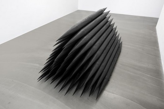 杨牧石,《刨除-栋梁》,房梁木,黑色喷漆,55件,每件长200 cm,直径9 cm,2015. Yang Mushi,