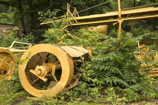 """《金光采矿区》局部。艺术家将这些遍布铜锈的庞大机械全部喷成金色,成为郑国谷近年颇多讨论的能量学试验场。/ Part of the """"Golden Mining Field"""". The artist painted these huge rusted machines in gold—a site of experimentation for Zheng Guogu's research on energy fields."""