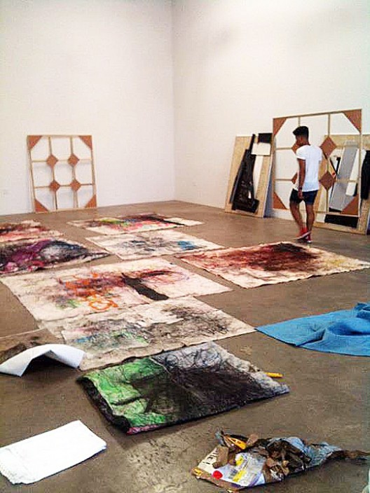 Oscar Murillo installing works at Nicodim Gallery, 2011 (courtesy of the artist and Nicodim Gallery)