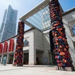 "AI Weiwei, ""Safe Passage,"" life jackets and inflatable raft, Dimensions variable, 2016 ""Reframe"", PVC, polycarbonate, rubber (set of 14), 650 x 325x75 cm (each), 2016 Installation view at Yokohama Museum of Art, Yokohama Triennale 2017, photo: Kato Ken © Ai Weiwei Studio, photo courtesy of Organizing Committee of Yokohama Triennale"