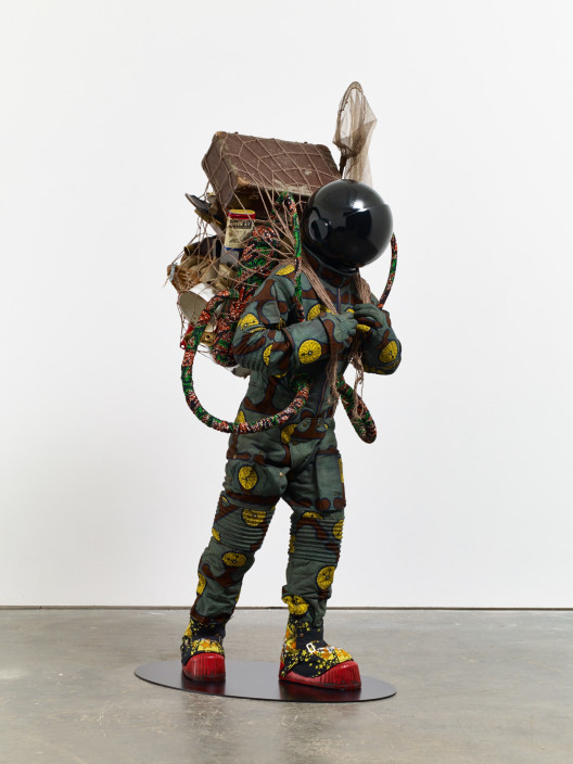 "Yinka Shonibare, ""Refugee Astronaut"", fibreglass mannequin, Dutch wax printed cotton textile, net, possessions, astronaut helmet, moon, boots and steel baseplate, 208 x 93 x 90 cm, 2015."