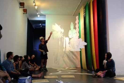 'Session 5: Sàn Art Laboratory' in group critique mode with Indonesian artist Rudy Atjeh explaining his work on view at San Art; November 2014 (image courtesy of Sàn Art)