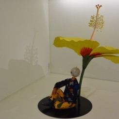 """Yinka Shonibare MBE, """"Boy Sitting Beside Hibiscus Flower"""", fibreglass mannequin, Dutch wax printed cotton textile, fibreglass, globe, leather and steel baseplate, 191 x 145 x 91 cm, 2015. (Courtesy the artist, Stephen Friedman Gallery, London and Pearl Lam Galleries, Hong Kong, Shanghai and Singapore)."""