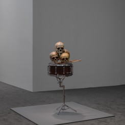 """Anri Sala, """"Still life in the Doldrums (d'après Cézanne)"""", four hand-painted human skulls, altered snare drum, carved American Maple drumsticks, altered snare stand, loudspeaker parts, and mono sound, 110 x 56 x 41 cm, 7:18 min, 2015. Maja Hoffmann / LUMA Foundation Photo: Maris Hutchinson / EPW Studio"""