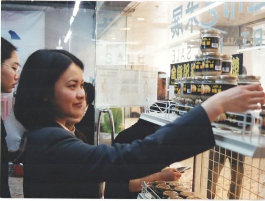 """1999年4月10日""""超市""""展的第一天,一位观众正在拿起朱昱作品《全部知识学的基础》——一瓶死人脑汁做成的浆糊 April 10th, 1999, a viewer looks at the first part of Zhu Yu's"""