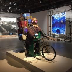 "Nam June Paik with Liu Xiaodong in background in ""Datumsoria"" at Chronus Art Center. 白南准,《成吉思汗的复原》,单频录像雕塑、电视、录像播放机、霓虹灯、彩色默片,260 x 100 x 220 cm,展览现场,新时线媒体艺术中心"