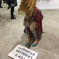 Squatting figure, art fair