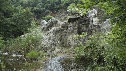 """艺术家陈翊朗在一个小宕口的石壁上创作了名为《山灵之主》的壁画。/ The artist Oscar Chan Yik Long created a mural entitled """"The Lord of the Mountain"""" on a small opening on the rock face."""