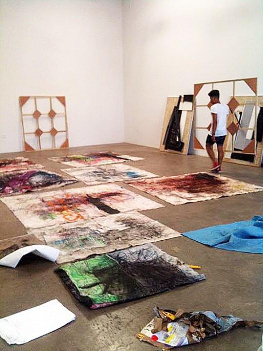 Oscar Murillo installing works at Nicodim Gallery, 2011 (courtesy of the artist and Nicodim Gallery)