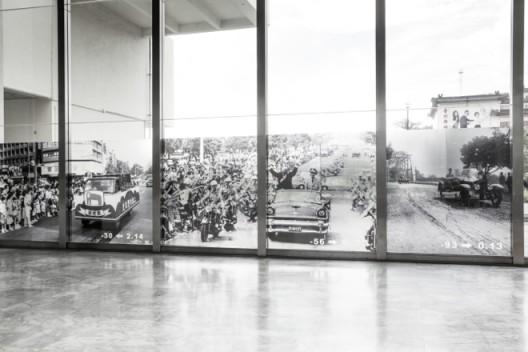 """黄立慧,《快乐天堂》,大图输出:1190 ×250公分,计算机割字,硅胶,隔热纸,音乐:快乐天堂,30位观众现场参与,尺寸视场地而定,2016(图片来源:联合报系。台北市立动物园于1986/9/14举行大搬家游行,在警车的前导下,六十五只动物分乘廿辆专车,从圆山动物园出发,驶往牠们的新家木栅动物园,吸引了廿万以上热情、好奇的民众夹道围观) Li-Hui HUANG, """"Happy Paradise"""", large format transparency: 1190 ×250 cm,vinyl letters, silicone, mylar window tint film, soundtrack: Happy Paradise, 30 audience participation on site, dimensions variable, 2016"""