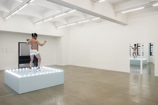 "费利克斯·冈萨雷斯-托雷斯,《""无题""(摇摆舞台)》,1991年。木、灯泡、丙烯涂料,摇摆舞者穿着银丝短裤、运动鞋,携带个人音乐设备。总尺寸可变。舞台 21 1/2 × 72 × 72 英寸。""每周都有些不一样的事物"",展览现场。美国纽约安德烈娅·罗森画廊。1991年5月2日 – 6月1日。© 费利克斯·冈萨雷斯-托雷斯基金会。纽约安德烈娅·罗森画廊惠允 / Felix Gonzalez-Torres, ""Untitled"" (Go-Go Dancing Platform), 1991. Wood, lightbulbs, acrylic paint and Go-Go dancer in silver lamé bathing suit, sneakers and personal listening device. Overall dimensions vary with installation. Platform: 21 1/2 x 72 x 72 in. Installation view of ""Every Week There is Something Different"". Andrea Rosen Gallery, New York. 2 May – 1 June 1991. © The Felix Gonzalez-Torres Foundation. Courtesy of Andrea Rosen Gallery, New York"
