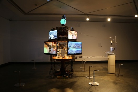 "Jon Kessler, ""The World is Cuckoo (Clock)"", mixed media with lights, motor, video cameras, monitors and Panerai watch, 162.56 cm × 337.82 cm × 271.78 cm, 2016"